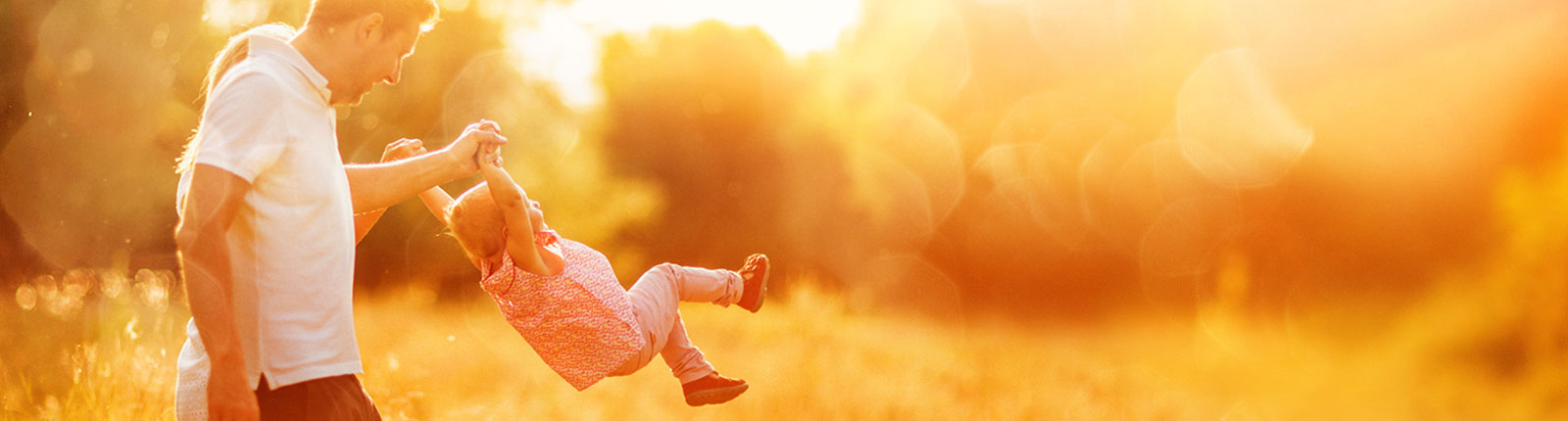 Family swinging little girl in air in sunny golden field